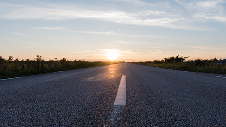 Extreme low angle view at an asphalt road straight forward by sunset Stock Photo