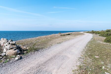 Winding dirt road along the coast at the swedish island Oland in the Baltic Sea