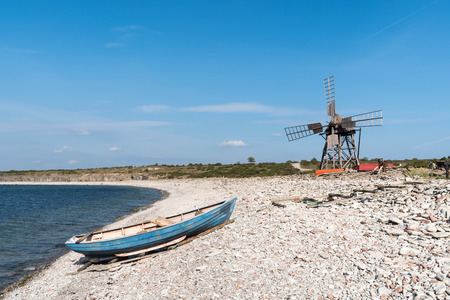 Blue rowing boat and an old windmill at the swedish island Oland in the Baltic Sea Stock Photo