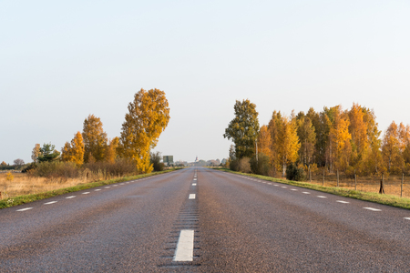 Sparkling fall colors by roadside in a low angle image of an asphalt country road Stock Photo