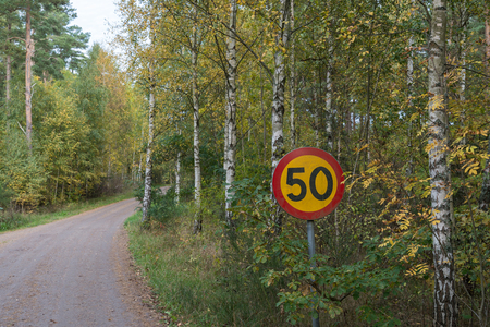 Speed limit traffic sign by a colorful gravel road at fall season Stock Photo