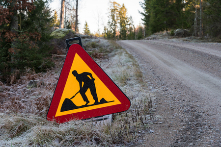 Traffic sign with warning for road work by a gravel road side in a forest Stock Photo