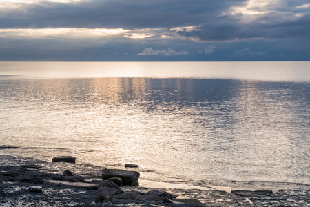 Seascape with sun reflections in the water and a dramatic sky Stock Photo