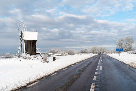 Old wooden windmill by roadside in winter season at the swedish island Oland