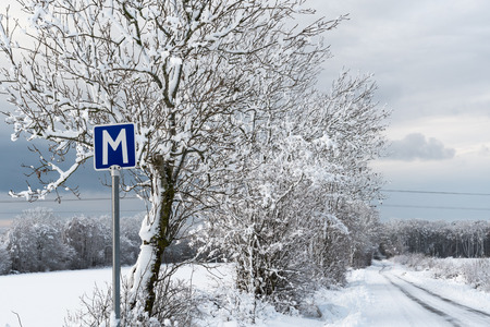 Passing place road sign by a narrow country road in winter season