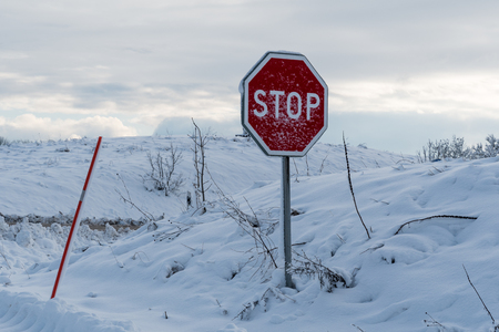 Snow covered stop traffic sign in a snowy landscape Stock Photo