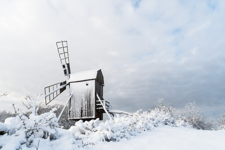 Old wooden windmill view in a snowy landscape at the swedish island Oland, the island of sun and wind Stock Photo