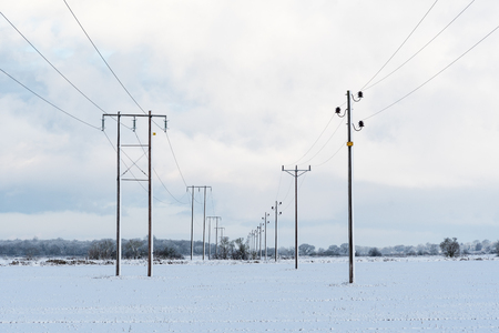 Electric power lines in a wintry landscape Stock Photo