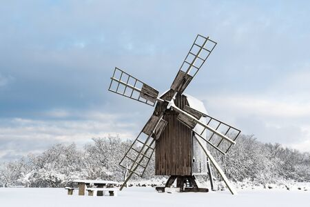 Old wooden windmill view in a snowy landscape at the swedish island Oland