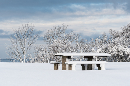Snow covered resting place with table and benches