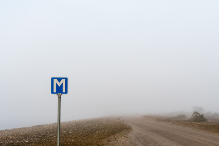 Passing place road sign by a country road in a misty landscape