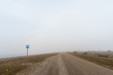Passing place by a narrow gravel road in a misty landscape