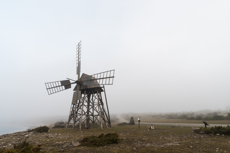 Old windmill in a foggy landscape at the swedish island Oland, a famous tourism site