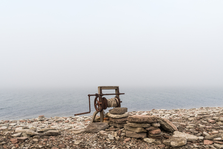Old rysty boat winch by a foggy coast