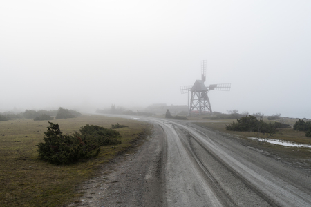 Old wooden windmill by roadside in the mist at the swedish island Oland Stock Photo
