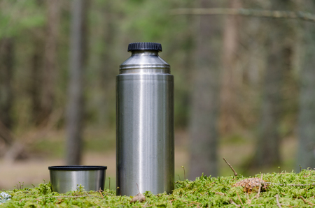 Steel bottle and a mug on a mossy ground in the forest