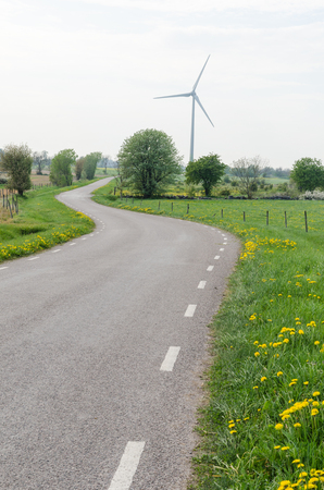 Wind turbine by a winding country road at the swedish island Oland