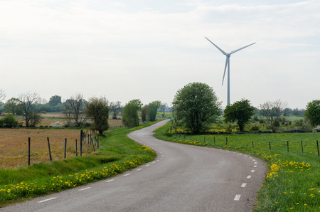 Winding road and a wind turbine at the swedish countryside in spring season