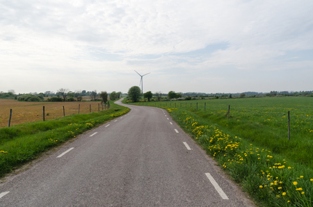 Country road by a windmill at spring season Stock Photo