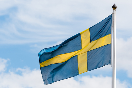 Swedish flag waving in the wind by a sky with white clouds