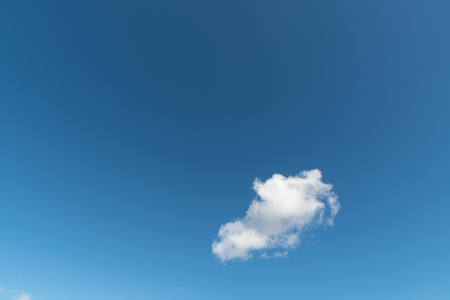 Blue summer sky with a single white cloud