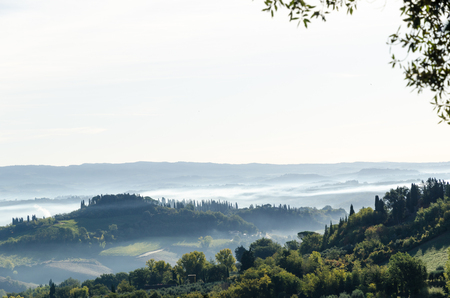 Misty Tuscany morning landscape seen from the village San Gimignano, Italy