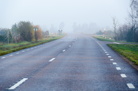 Foggy road by fall season in the first morning sunshine