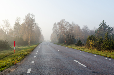 Misty country road by the first morning sunshine at fall season Stock Photo