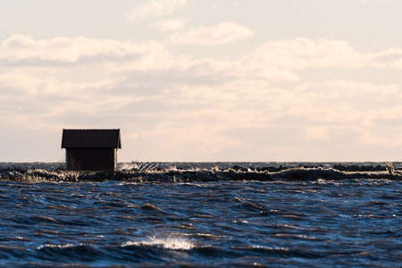 Fishing cabin by seaside in a stormy water