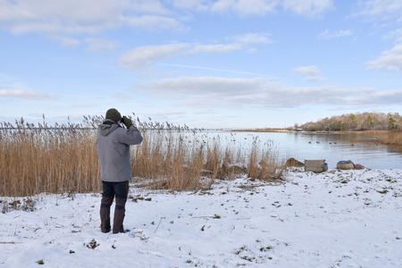 Birder by a bay in winter season at the swedish island Oland in the Baltic Sea