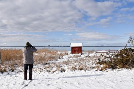 Birdwatcher looking for birds in winter season by the coast of swedish island Oland
