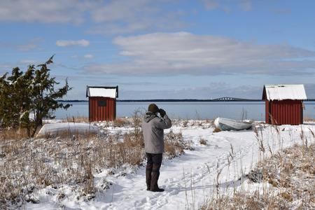 Birder watching at birds by the coast in winter season at the swedish island Oland