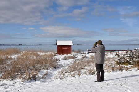 Male birder by the coast in winter season at the swedish island Oland Stock Photo