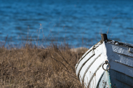 Front view of an old abandoned wooden fishing boat by seaside