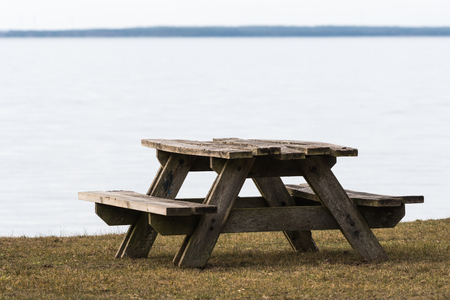 Weathered wooden table and benches by the coast with calm water