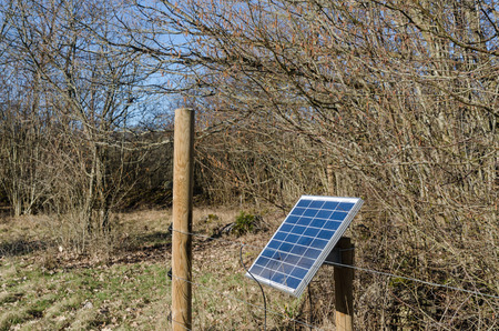 Solar power system by a fence in a rural landscape Imagens