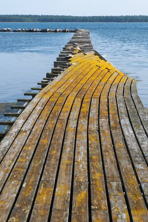 Broken old jetty in yellowish color at the swedish island Oland