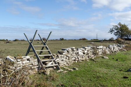 Wooden stile crossing an old dry stone wall at the island Oland in Sweden