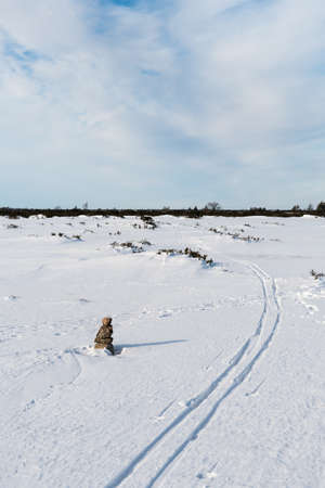 Stone cairn and ski tracks in a wintry landscape  on the island Oland in Sweden