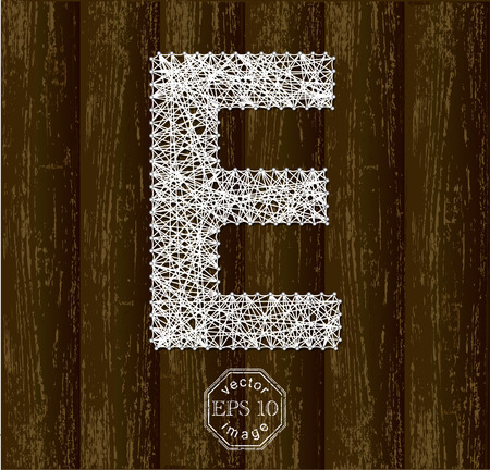 threads: Letter E, made with threads on pins on wooden background