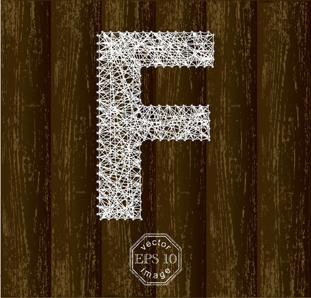 threads: Letter F, made with threads on pins on wooden background