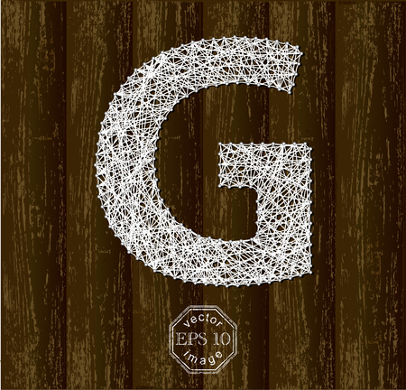 threads: Letter G, made with threads on pins on wooden background
