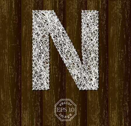 background part: Letter N, made with threads on pins on wooden background. Part of collection.