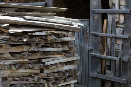 neatly stacked: Firewood neatly stacked near wooden shed