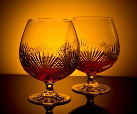 two cut glass brandy glasses in low light
