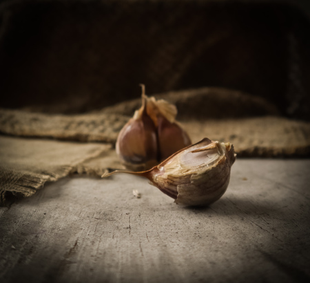 Garlic cloves and natural linen napkin on rustic wooden background 免版税图像
