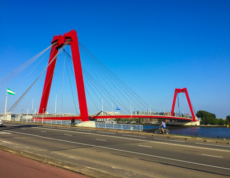 Willemsbrug bridge spanning the Nieuwe Maas river in Rotterdam, The Netherlands. Red bridge pylons and cables against blue sky