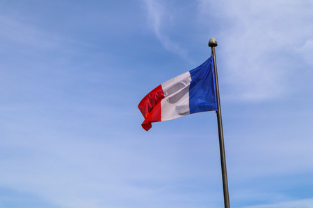The national flag of France on the flagpole develops in the wind against the blue sky Reklamní fotografie