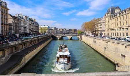 Paris  France - April 5, 2019: Beautiful cityscape of Paris, Saint-Michel bridge across Seine river and a tourist ship with tourists