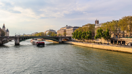Beautiful cityscape of Paris, bridge Pont Sully across Seine river and a ship. France. April 2019 Editöryel